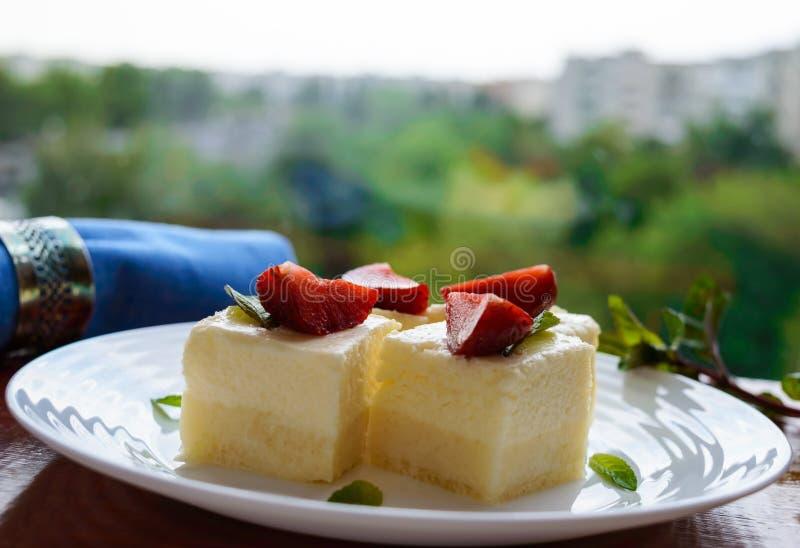 Fromage blanc sensible et soufflé crémeux sous forme de cubes, décorant des feuilles en bon état et des fraises fraîches photographie stock libre de droits