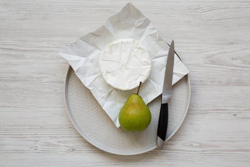 Fromage de camembert et poire fraîche d'un plat sur un fond en bois blanc Nourriture pour le vin Configuration plate, vue supérie photographie stock