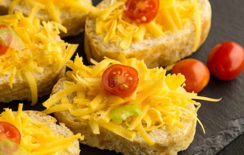 Fromage de cheddar et tomates-cerises râpés sur des tranches de baguette photos libres de droits
