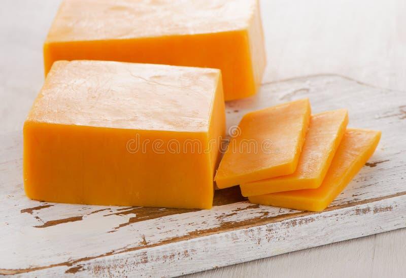 Fromage de cheddar sur la planche à découper en bois blanche photographie stock