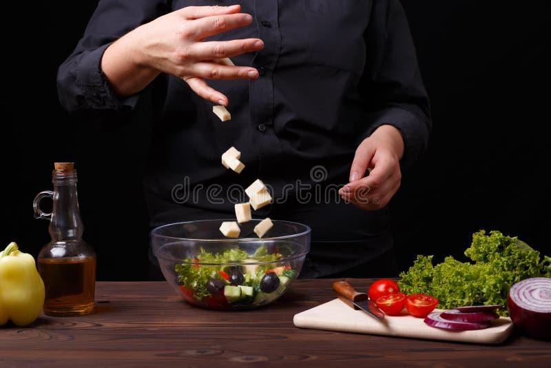 Fromage de chute de chef dans une cuvette avec de la salade grecque, procédé de cuisson photos stock