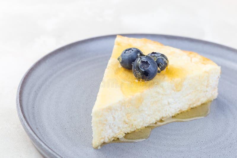 Fromage de cocotte ou de cheesecake, garni de bleuet et de miel, sur plaque grise, horizontal, espace de copie photographie stock libre de droits
