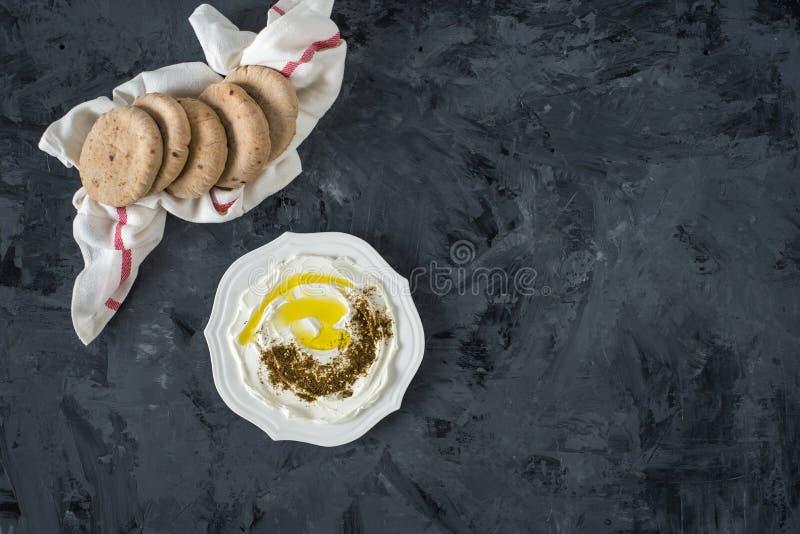 """Fromage du lait de la chèvre blanche molle du Moyen-Orient de labaneh de Labneh avec l'huile d'olive, olives, za """"atar, citron, a images libres de droits"""