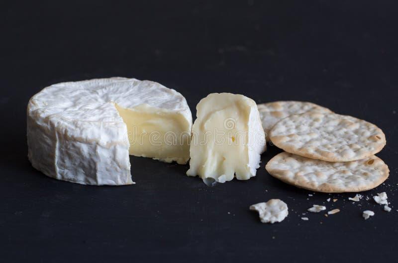 Fromage et biscuits crémeux mous de camembert sur le fond noir - photographie stock libre de droits