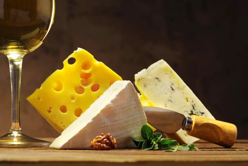 Fromage et vin dans un verre sur un conseil en bois photos stock