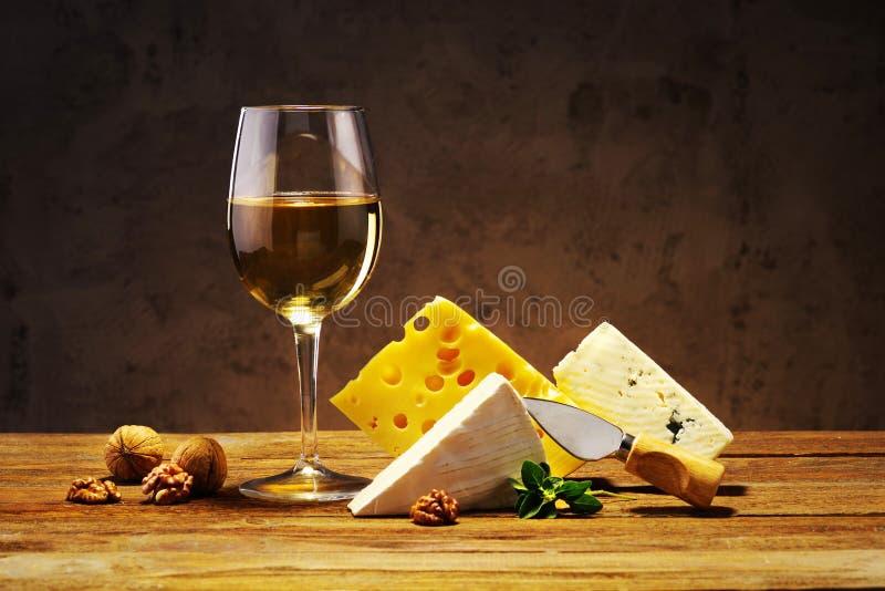 Fromage et vin dans un verre sur un conseil en bois photographie stock libre de droits