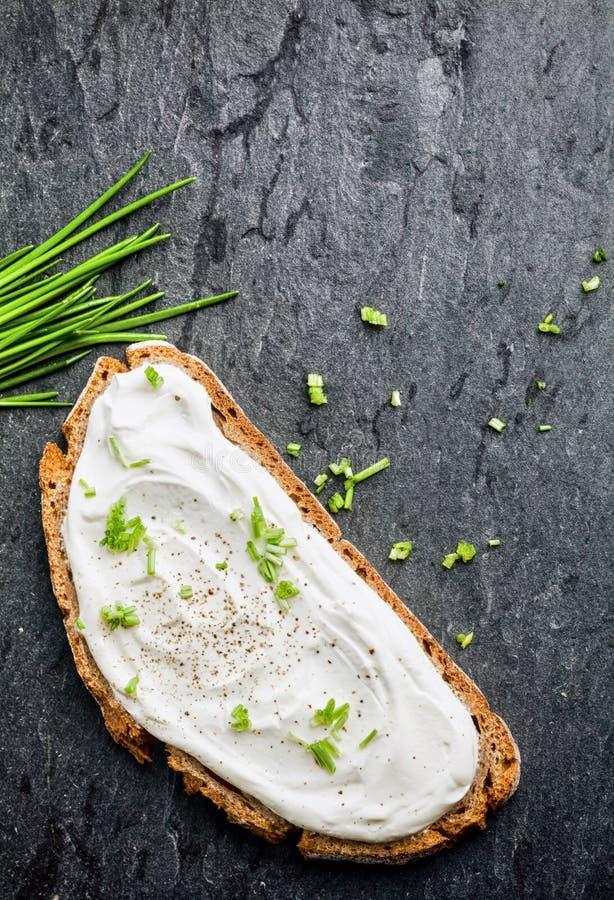 Fromage fondu et ciboulette sur le pain de blé entier photos libres de droits