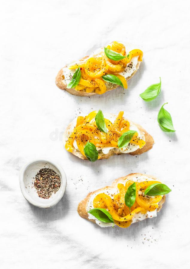 Fromage fondu, paprika jaune rôti, bruschette de basilic dessus sur le fond clair, vue supérieure Copiez l'espace photographie stock
