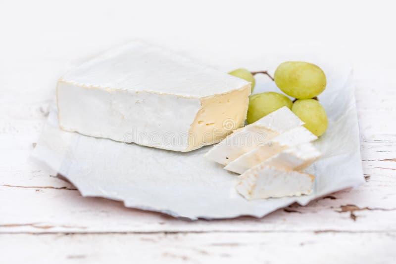 Fromage frais de brie avec des tranches et raisin sur rustique blanc sur un courtiser photos stock