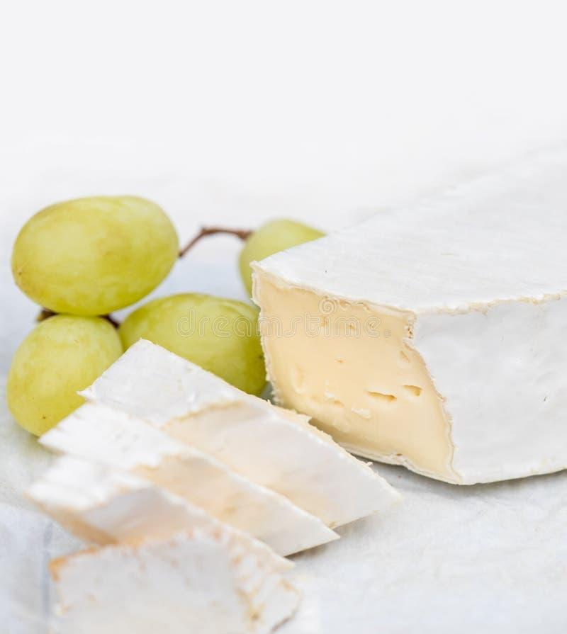 Fromage frais de brie avec des tranches et raisin sur rustique blanc sur un courtiser photographie stock