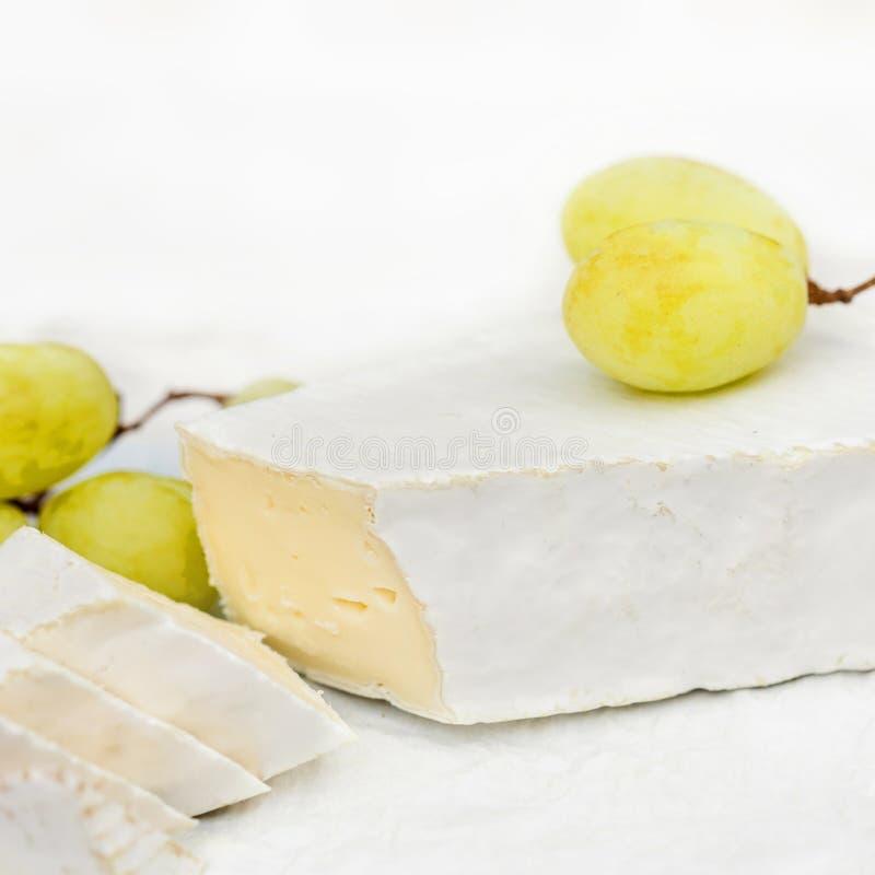 Fromage frais de brie avec des tranches et raisin sur rustique blanc sur un courtiser photo libre de droits