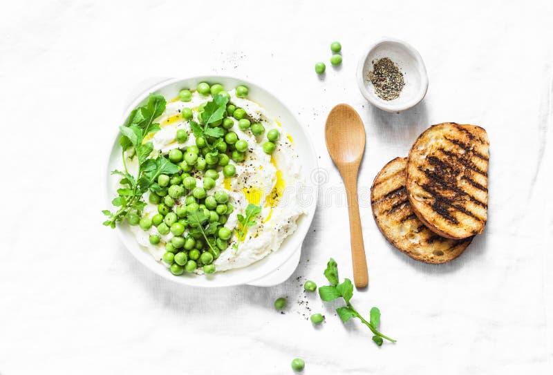 Fromage frais de ricotta avec les pois, l'huile d'olive, le poivre et les herbes sur un fond clair, vue supérieure Nourriture d'a images libres de droits