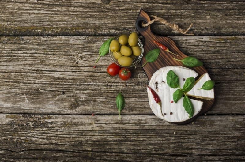 Fromage français - camembert rond avec des feuilles, des poivrons, des tomates et des olives de basilic sur un fond en bois drape photos stock