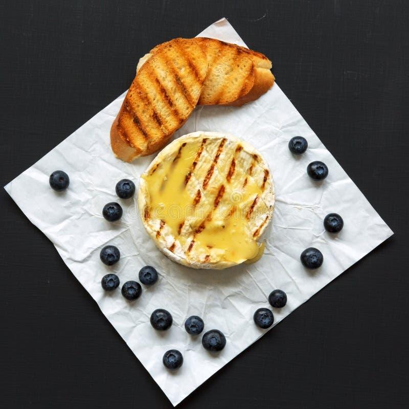 Fromage grillé de camembert en papier avec des pains grillés, des myrtilles et des noix sur un fond noir Nourriture pour le vin V photo libre de droits