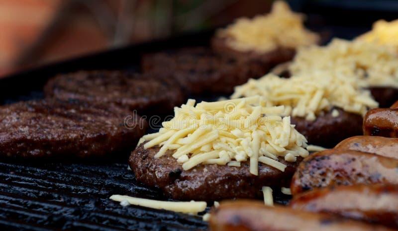 Fromage râpé empilé sur un beefburger grillé tout entier image stock