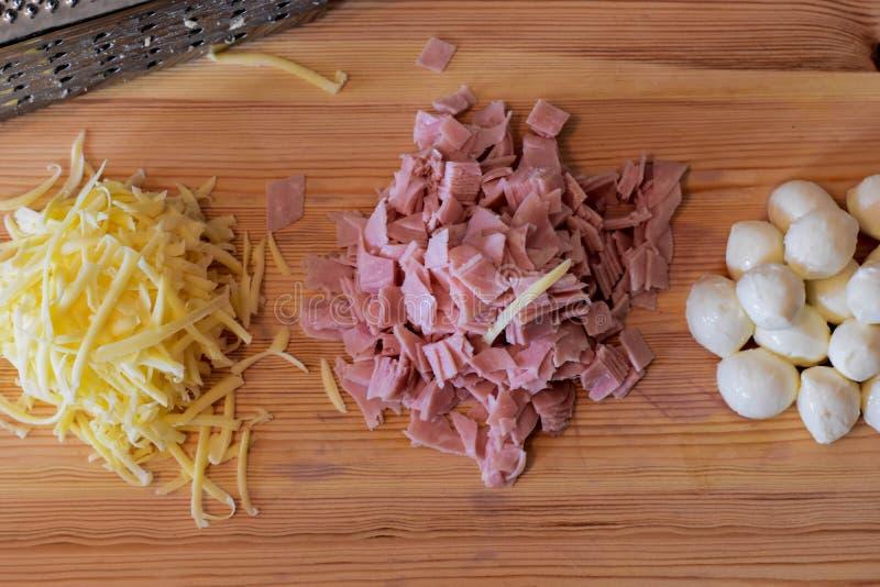 Fromage râpé, jambon coupé, boules de mozzarella et râpe sur le fond en bois images libres de droits