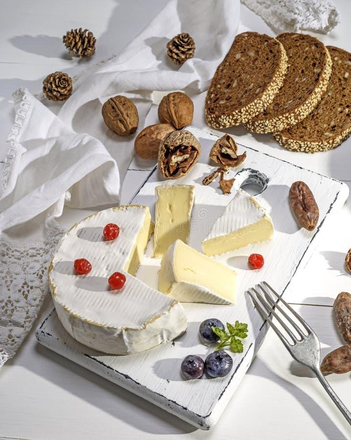 Fromage rond de camembert sur un conseil en bois blanc photographie stock