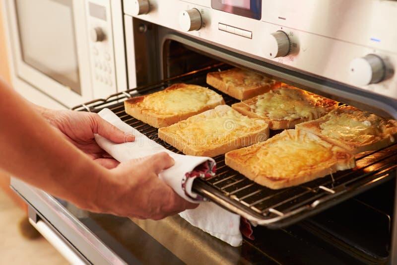 Fromage sur le pain grillé étant grillé en four photo libre de droits