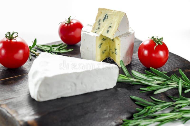 Fromages assortis sur planche en bois Camembert, fromage au lait bleu, mozzarella aux tomates photo stock