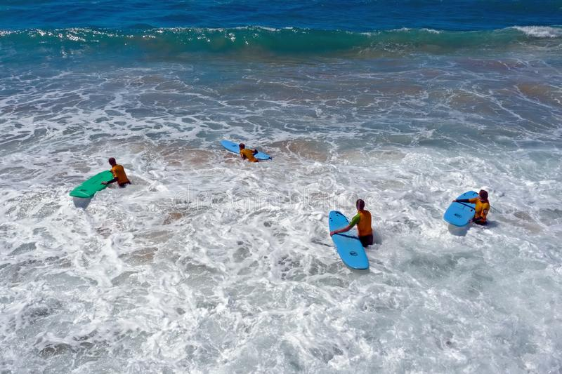 Fromsurfers aéreos que obtêm lições surfando no oceano imagem de stock