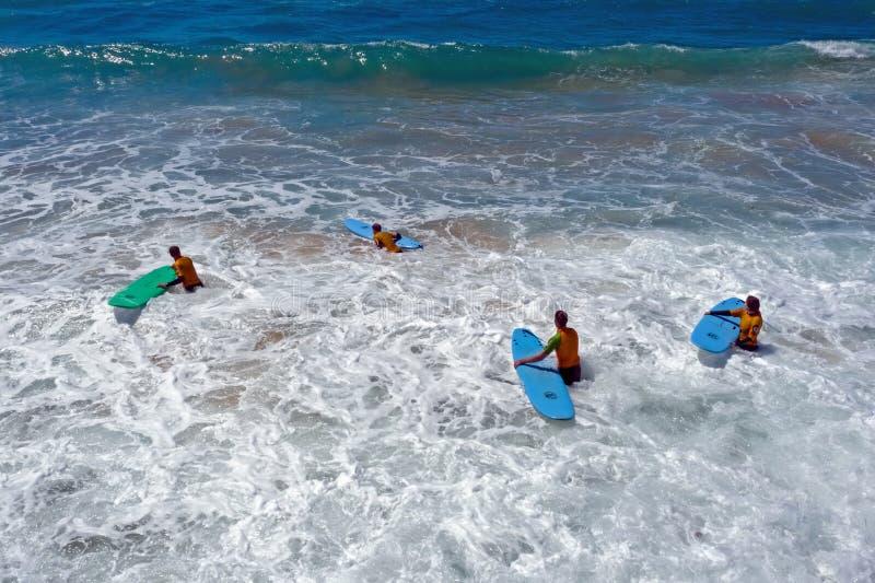 Fromsurfers aerei che ottengono le lezioni praticanti il surfing nell'oceano immagine stock