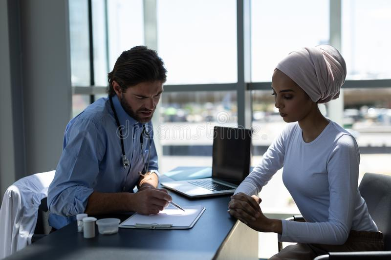 Disabled mixed-race woman and Caucasian male doctor interacting with each other royalty free stock photography