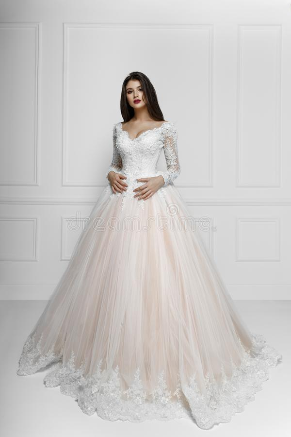 Frontal view of a fashion model in long elegant wedding dress, isolated on white background. royalty free stock images