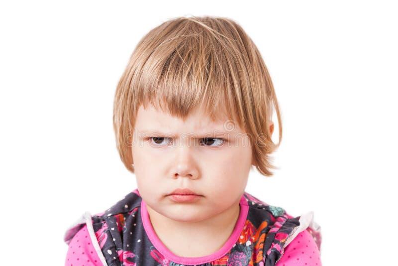 Froncements de sourcils fâchés de bébé blond, portrait de studio image stock