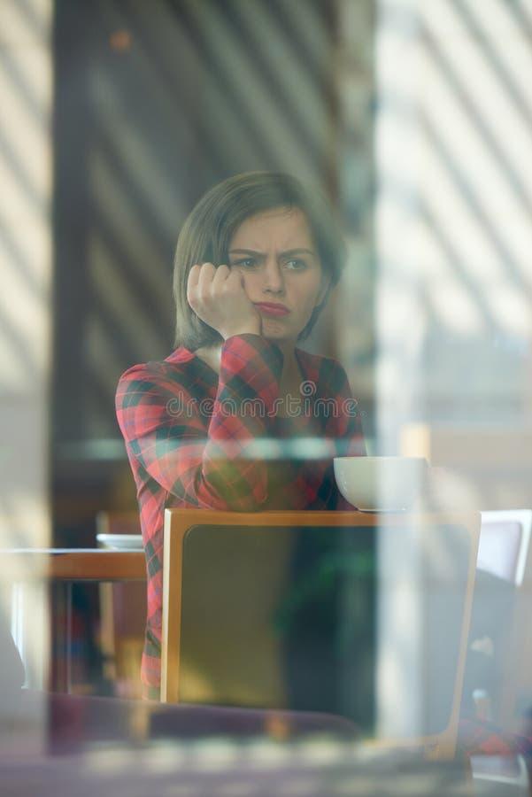 Fronsende jonge vrouw in koffie royalty-vrije stock fotografie