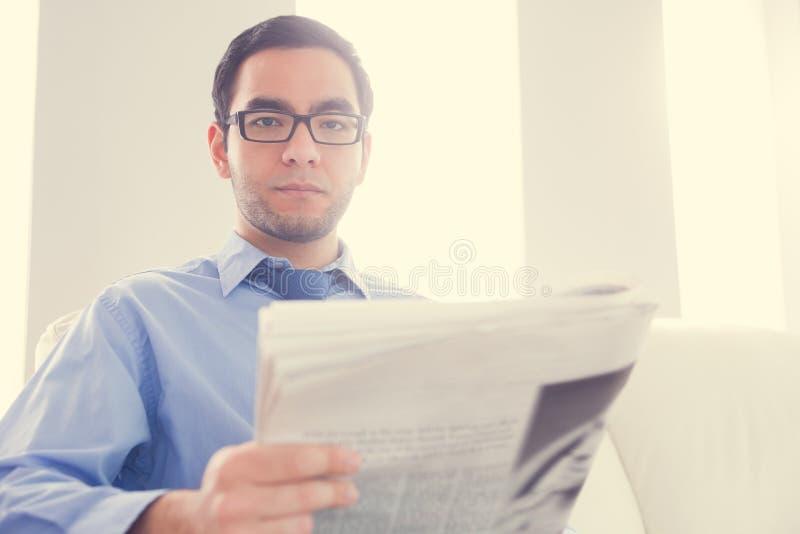 Fronsende mens die camera en het houden van een krant bekijken royalty-vrije stock foto's