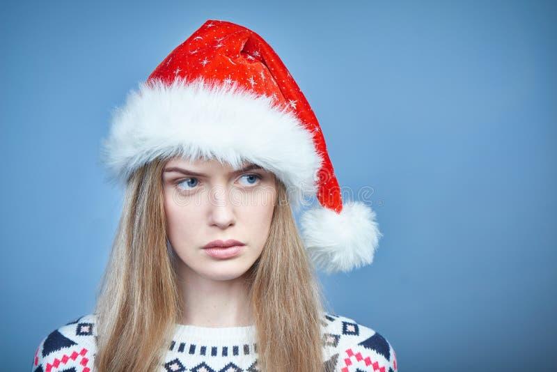 Fronsende ongerust gemaakte vrouw die Kerstmanhoed dragen die opzij eruit zien royalty-vrije stock afbeeldingen