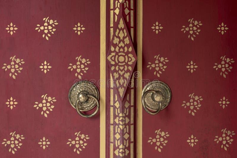 Front of Beautiful red wooden door to Bhutan style background with door knob of gold metal. Temple door royalty free stock photography