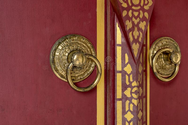 Front of Beautiful red wooden door to Bhutan style background with door knob of gold metal. royalty free stock image