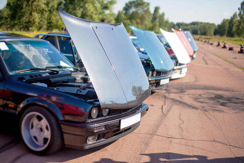 The front of black old car surrounded by the same machines with open hood stock photos