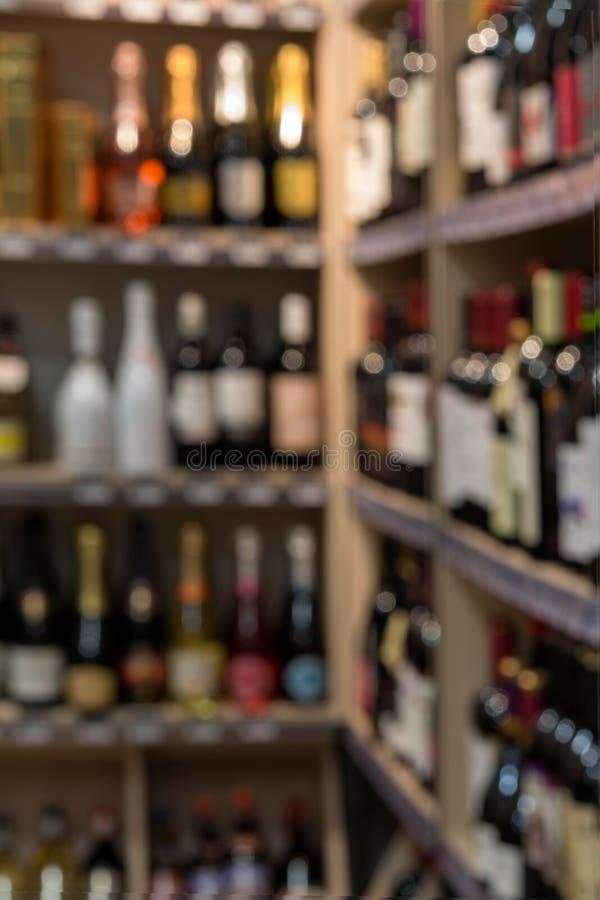 Front of blurred background. Blurred alcohol bottles on shelves in supermarket. stock photo