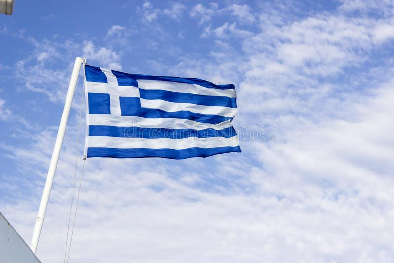 Front bottom shot of colorful waving greece flag with blue open sky background at Izmir in Turkey royalty free stock images