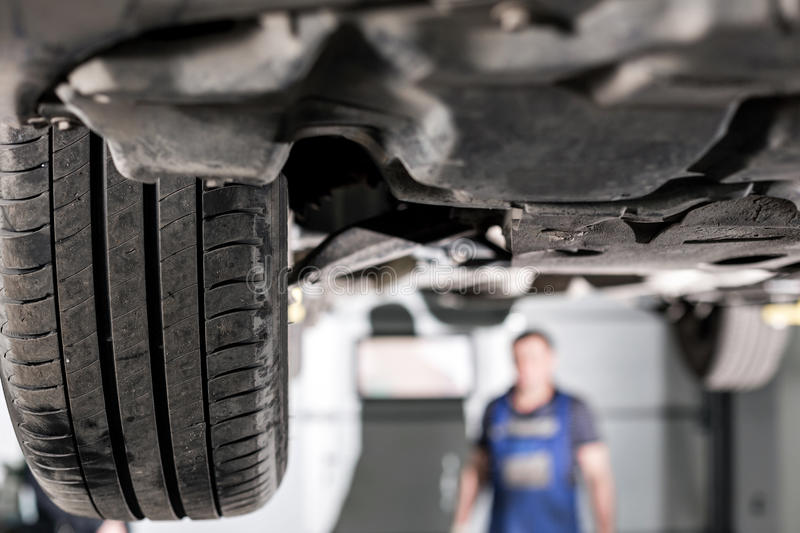 Front car suspension. the garage mechanic raised the car on the lift.  stock image