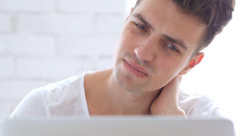 Front Close-Up dell'uomo stanco che prova a rilassarsi i muscoli del collo sul lavoro immagine stock