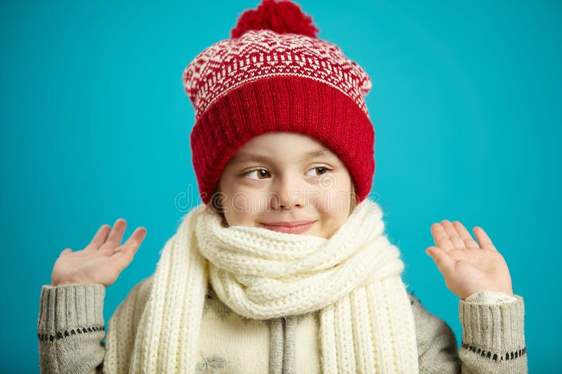 Front close-up portrait of little girl in red winter hat and white scarf on blue background, raised her hands up, looks stock photo