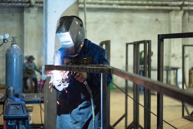 Front close-up of a worker wearing protective gear. With mask and a leather apron, welding together two pieces of square pipes into a frame, with several stock photos