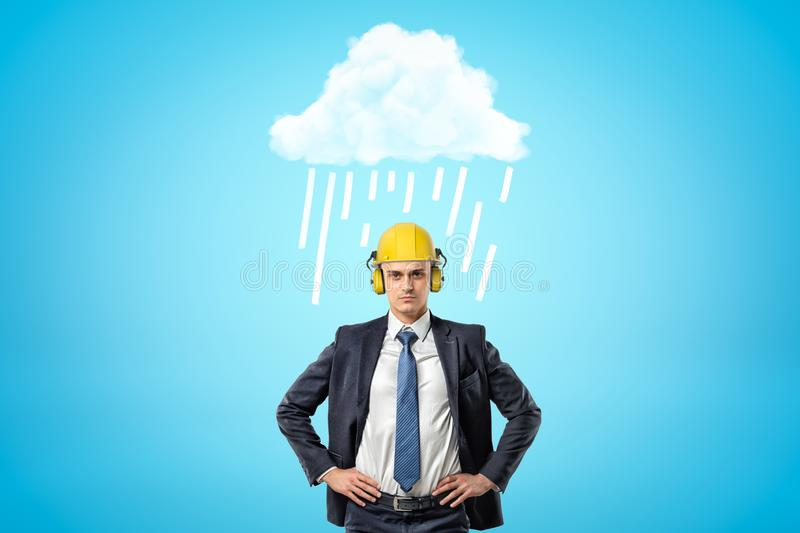 Front crop image of businessman in yellow hard hat with ear defenders, standing with hands on hips under white raining. Cloud. Face future with confidence. Cope stock images