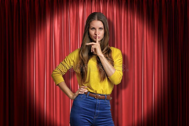 Front crop view of pretty woman standing in spotlight at red stage curtain, one hand on hip, other hand doing silencing royalty free stock photography
