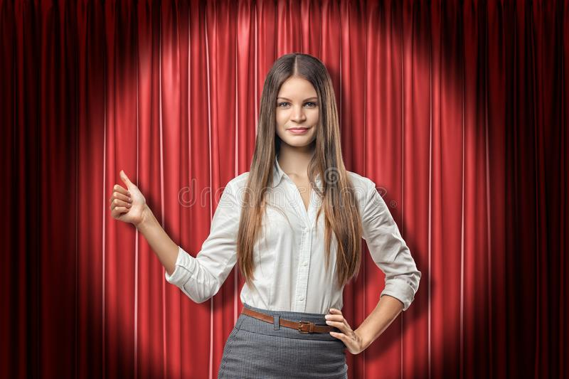 Front crop view of young attractive businesswoman with long straight hair standing in spotlight against red stage stock images