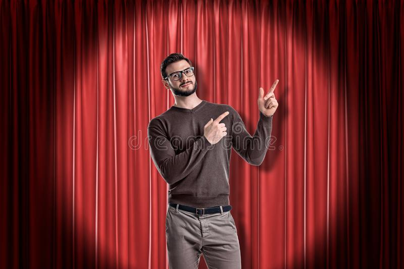 Front crop view of young handsome man in casual clothes standing in spotlight against red stage curtain and pointing up royalty free stock photo