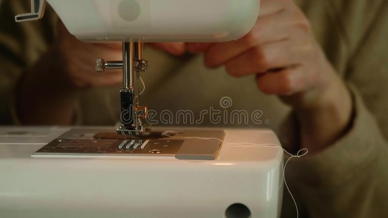 Front and defocused view of caucasian woman`s hands. Hands put stitch into needle before starting to sew stock photography