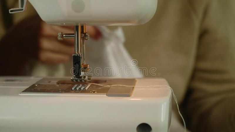 Front and defocused view of caucasian woman`s hands. Hands start to sew white material on sewing machine. stock photo