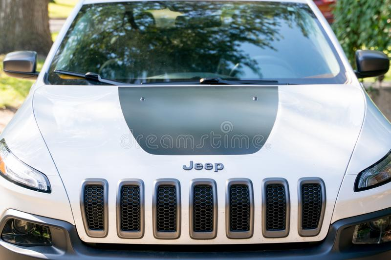 Front detail hood grill of a white Jeep Cherokee Trailhawk SUV. Vehicle stock images