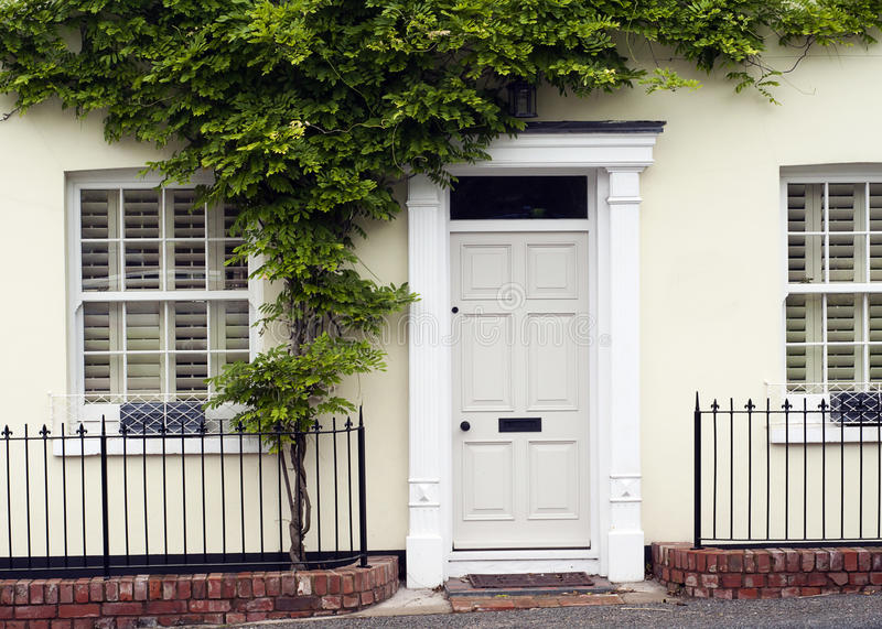 Front door. White front door entrance and old style window of a white house or a cottage with green wall plant and iron fence royalty free stock photo