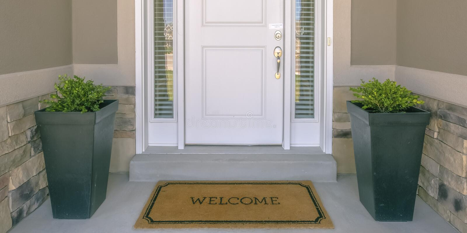 Front door with doormat plants and glass panel. White front door of a house with the word welcome printed on the brown doormat. Ornamental plants and glass stock photos