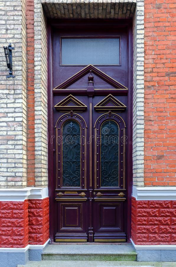 Front door, double purple front doors with geometric elements, and glass. Brick wall royalty free stock photos